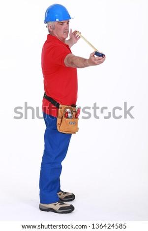 Senior plumber standing on white background - stock photo