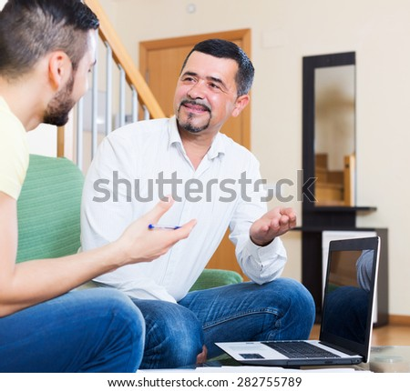 Senior positive father helping young son to fill application form - stock photo
