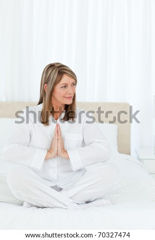 Senior practicing yoga on her bed at home