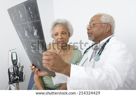 Senior practitioner  and patient examine xray - stock photo