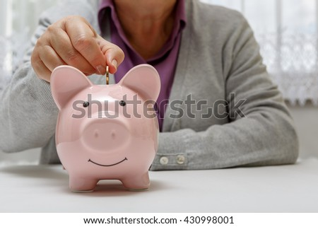 Senior puts money into the piggy bank