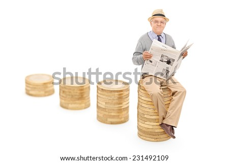 Senior reading the news seated on a pile of coins with the focus on the front pile isolated on white background - stock photo