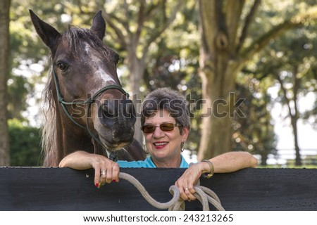 Senior retired elderly older woman lady smiling and happy with brown horse leaning over a fence signifying good retirement and health in old age - stock photo