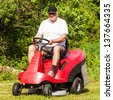 Senior retired male citizen driving a red lawn mower (tractor) and cutting grass in the yard - stock photo