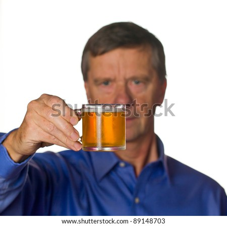Senior retired male with a cool glass of beer in a very small tankard with the man out of focus - stock photo