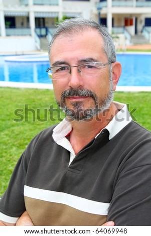 Senior retired man glasses relax on vacation garden pool - stock photo