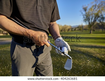 senior retired man with irons and putter on golf course - stock photo