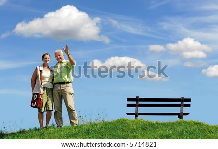 senior retired smiling couple, man greeting with his hand, walking outdoors on green grass hill with bench and white clouds on blue sky background - stock photo
