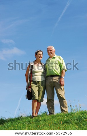 senior retired smiling couple walking outdoors on green grass hill with blue sky background - stock photo