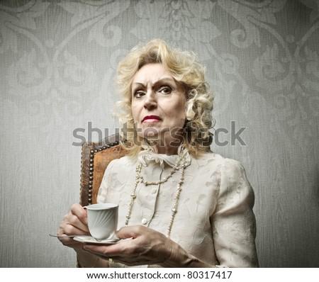 Senior rich woman having a cup of tea - stock photo
