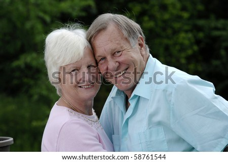 Senior romantic couple shares some intimate moments in their garden. - stock photo
