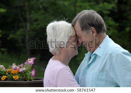 Senior romantic couple shares some intimate moments in their garden.