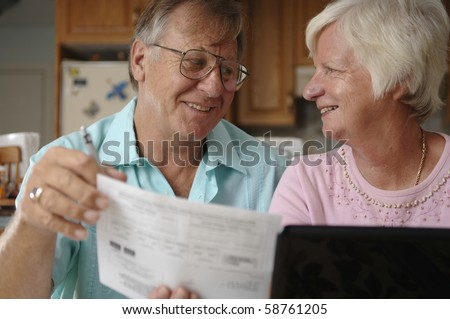 Senior romantic couple uses computer and the Internet to do some e-banking from their rural home.
