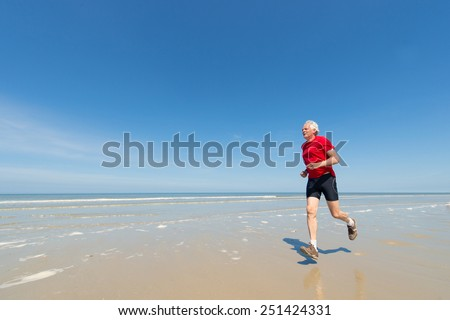 Senior runner at the beach - stock photo