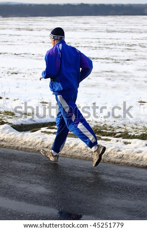 Senior runner while training for a competition in winter - stock photo