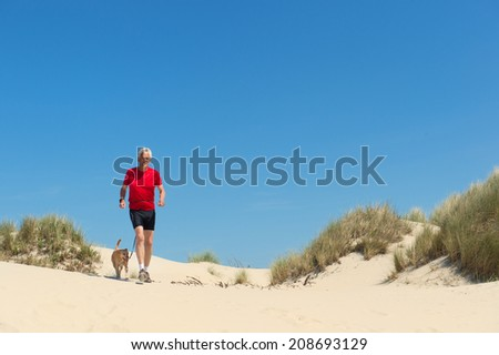 Senior runner with dog in nature dunes - stock photo