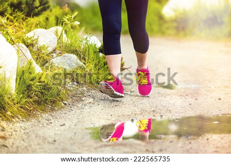 Senior runner woman feet running in beautiful nature reflecting in puddle, closeup on feet - stock photo
