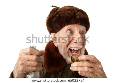 Senior Russian Man in Fur Cap and Jacket with Vodka - stock photo