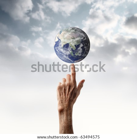 Senior's hand holding the earth on its finger - stock photo