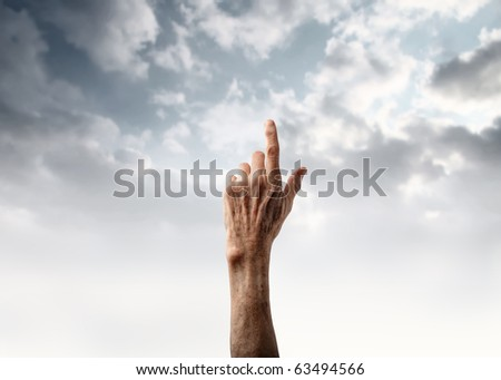 Senior's hand pointing at the sky - stock photo