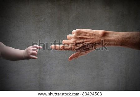 Senior's hand touching a little child's hand - stock photo