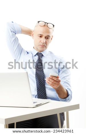 Senior sales man working on laptop and using mobile against white background.