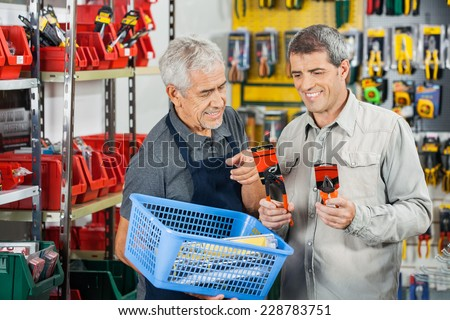 Senior salesman assisting customer in buying pliers at hardware store - stock photo