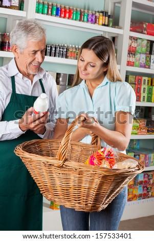 Senior salesman assisting female customer buying groceries in supermarket - stock photo