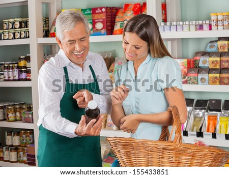 Senior salesman assisting female customer in shopping groceries at store - stock photo