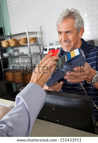 Senior salesman holding electronic reader while customer paying through smartphone