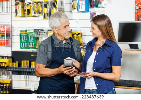 Senior salesman holding electronic reader while female customer paying through smartphone in hardware store - stock photo