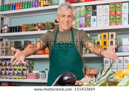 Senior salesman with arms outstretched in supermarket - stock photo