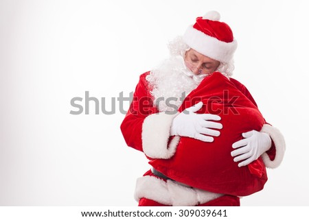 Senior Santa Claus is holding a red bag of present. He is leaning his head on it and sleeping. The man closed his eyes with relaxation. Isolated and copy space in left side - stock photo