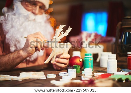 Senior Santa man painting wooden deer with gouache - stock photo