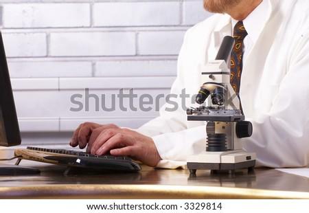 Senior scientist and microscope - stock photo
