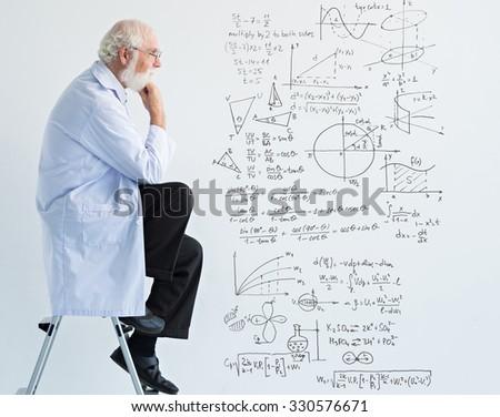 Senior scientist sitting on ladder and thinking - stock photo