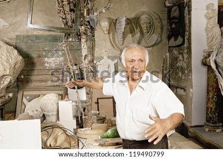 Senior sculptor in workshop gesturing while talking - stock photo