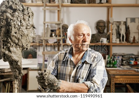 Senior sculptor standing in workshop against sculpture and kneads clay - stock photo