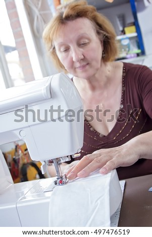 Senior seamstress sewing a piece of white cloth on her electric sewing machine