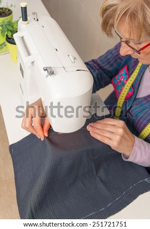 Senior seamstress woman working with clothing item on a sewing machine. Selective focus on woman face. - stock photo