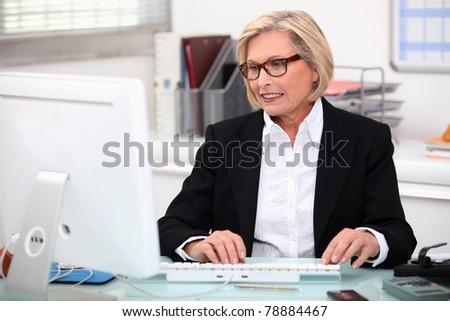 Senior secretary at work - stock photo