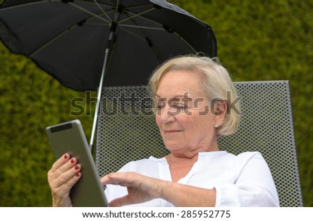 Senior serene woman wearing white shirt and lieing an a camp bed on the green lawn of the garden while using a wireless black tablet PC and showing thumb up, in a warm day of summer - stock photo