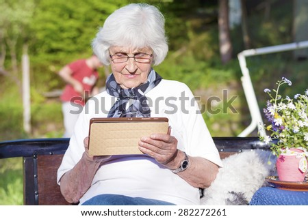 Senior serene woman wearing white shirt and sitting on a wooden bench in the garden while using a wireless tablet PC .Reading concept