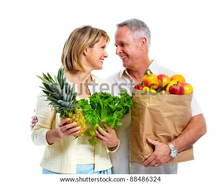 Senior shopping couple with grocery items . Isolated over white background. - stock photo
