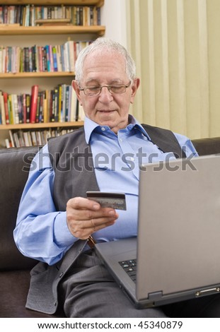 senior shopping online with laptop on sofa - stock photo