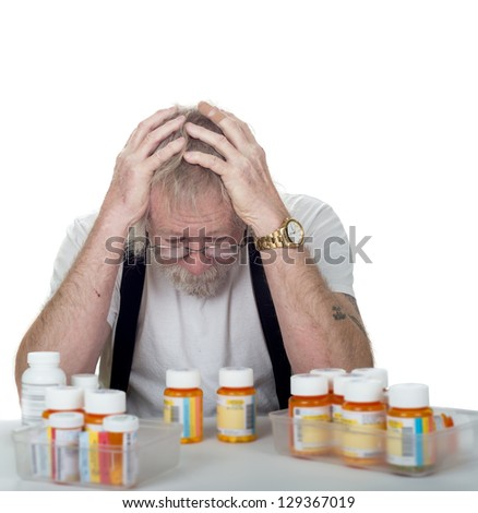 senior sitting behind a lot of pill bottles holding his head in his hands isolated on white - stock photo