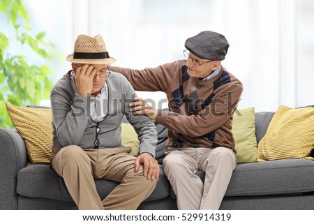 Senior sitting on a sofa and comforting another senior