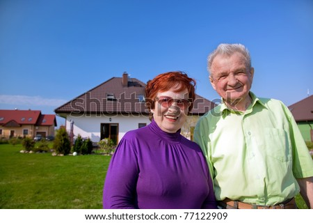 Senior smiling couple in front of their new house - stock photo