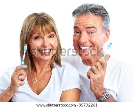 Senior smiling couple with toothbrushes. Over white background. - stock photo