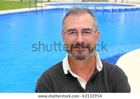 Senior smiling man vacation in blue pool happy retired